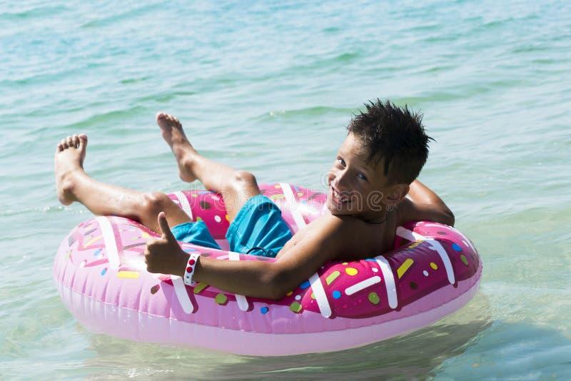Niño con el anillo inflable en el mar fotos de archivo