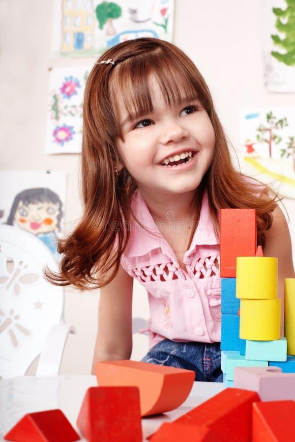 Niño con el bloque de madera en sitio del juego. imagen de archivo libre de regalías