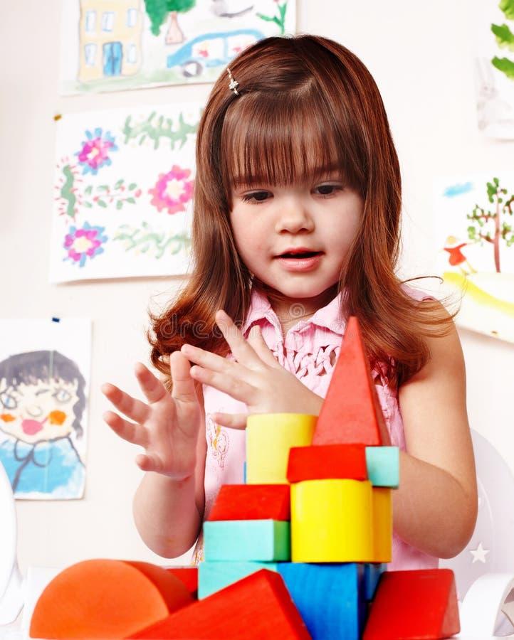 Niño con el bloque de madera en sitio del juego. foto de archivo