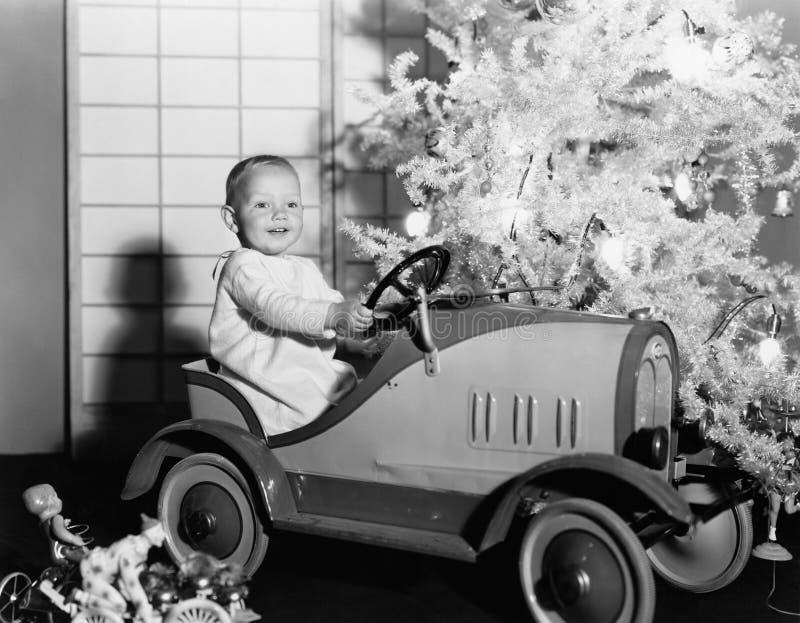 Niño con el coche del juguete debajo del árbol de navidad (todas las personas representadas no son vivas más largo y ningún estad fotos de archivo libres de regalías