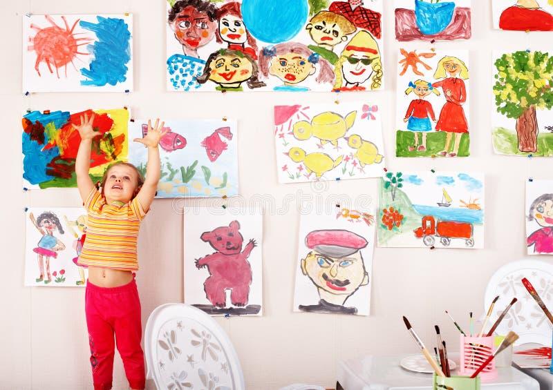 Niño con el cuadro y cepillo en sala de juegos. foto de archivo libre de regalías