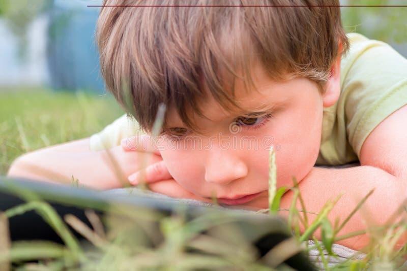 Niño con el ipad en hierba verde Retrato del muchacho con la tableta Problemas del ojo causados usando las tabletas demasiado Cui fotografía de archivo libre de regalías