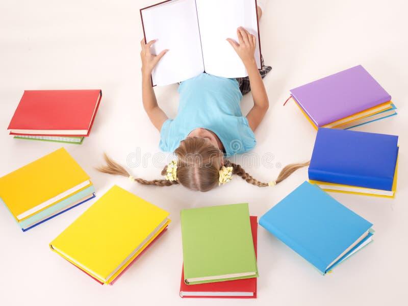 Niño con el libro abierto que miente encendido detrás. foto de archivo libre de regalías