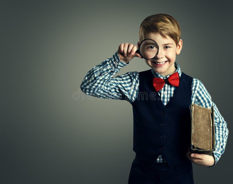 Niño con el libro y la lupa, educación del niño de la escuela fotografía de archivo