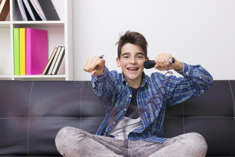 Niño con el micrófono que canta fotografía de archivo