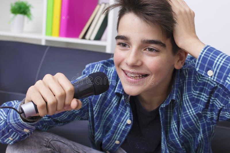 Niño con el micrófono que canta fotografía de archivo libre de regalías