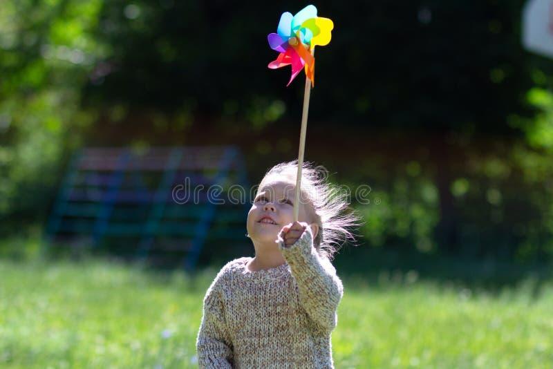 Niño con el molinillo de viento en el parque del verano que mira el juguete foto de archivo libre de regalías