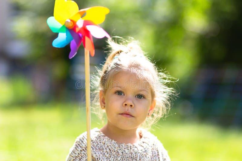 Niño con el molinillo de viento en el parque del verano que mira la cámara fotos de archivo