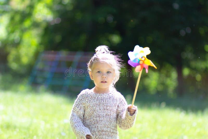 Niño con el molinillo de viento en el parque del verano que mira la cámara imagen de archivo libre de regalías