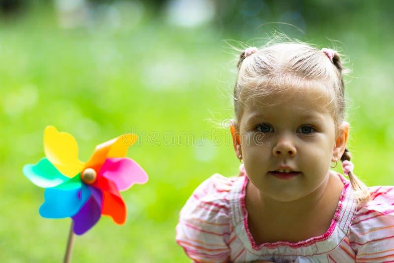 Niño con el molinillo de viento en el parque del verano que mira la cámara foto de archivo libre de regalías