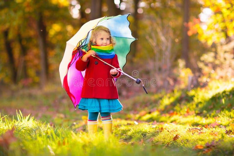 Niño con el paraguas que juega en lluvia del otoño imagen de archivo libre de regalías