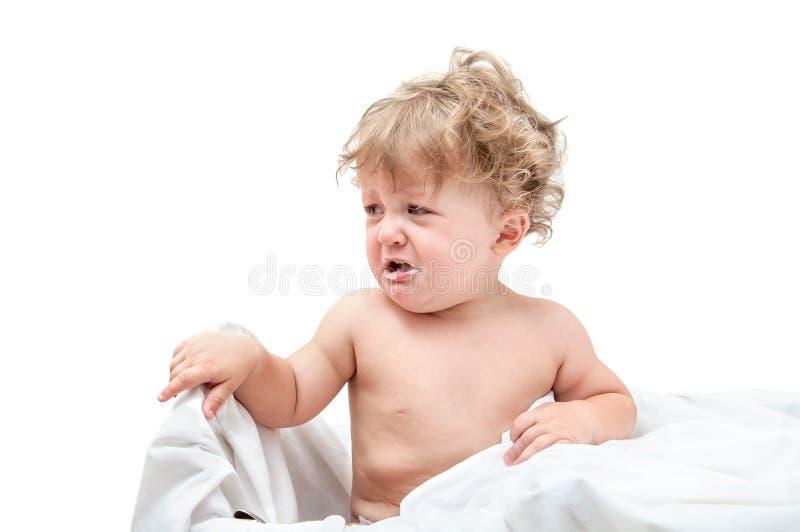 Niño con el pelo rizado que se sienta en la tabla foto de archivo libre de regalías
