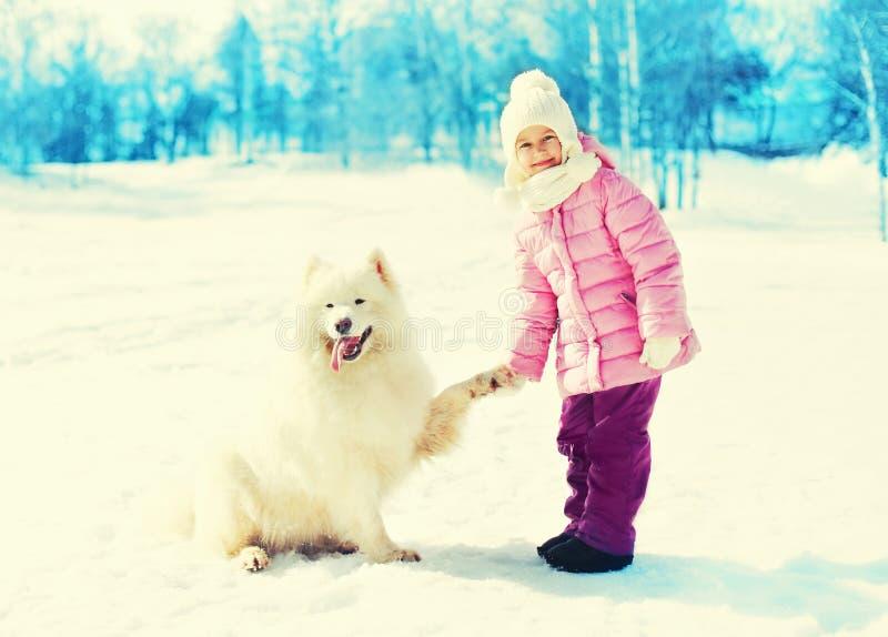 Niño con el perro blanco del samoyedo que juega invierno imágenes de archivo libres de regalías