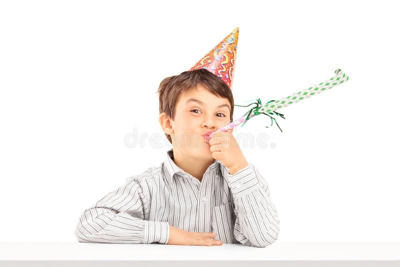 Niño con el sombrero del partido que sopla un cuerno del favor foto de archivo
