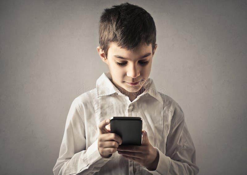 Niño con el teléfono imagenes de archivo