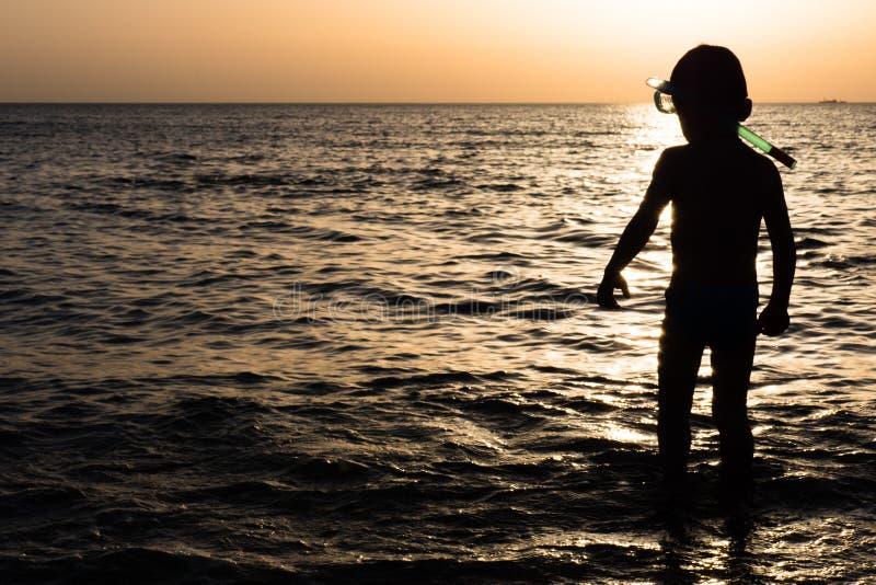 Niño con el tubo respirador y máscara para zambullirse en el fondo de la puesta del sol del mar foto de archivo
