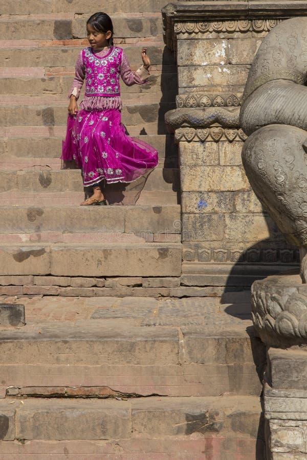 Niño con el vestido tradicional que va abajo de las escaleras de Nyatapola fotografía de archivo