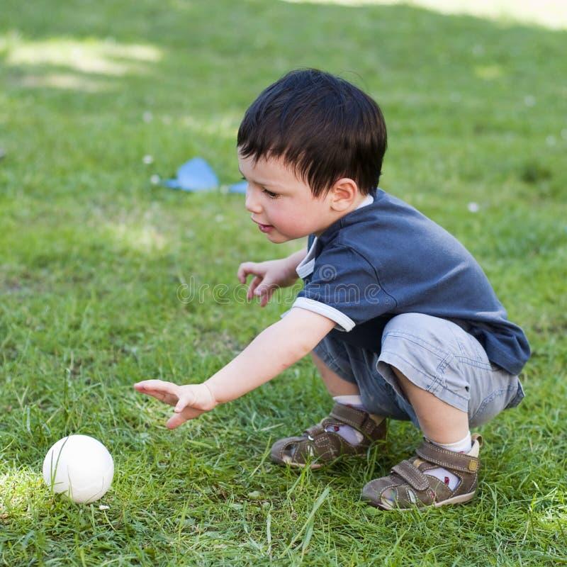 Niño con la bola en jardín fotografía de archivo