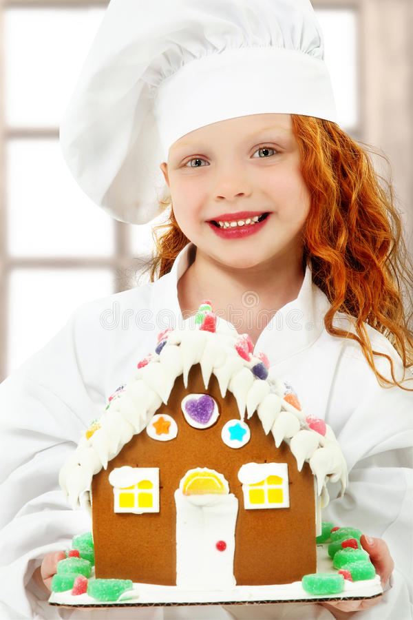Niño con la casa de pan de jengibre en la Navidad como cocinero fotografía de archivo libre de regalías