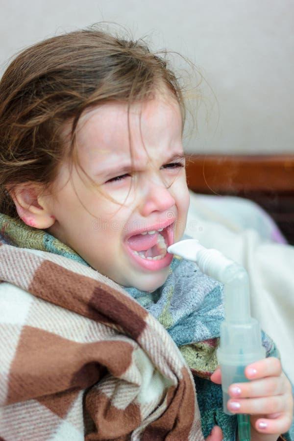 Niño con la enfermedad respiratoria que hace la inhalación con el inhalador imagen de archivo libre de regalías