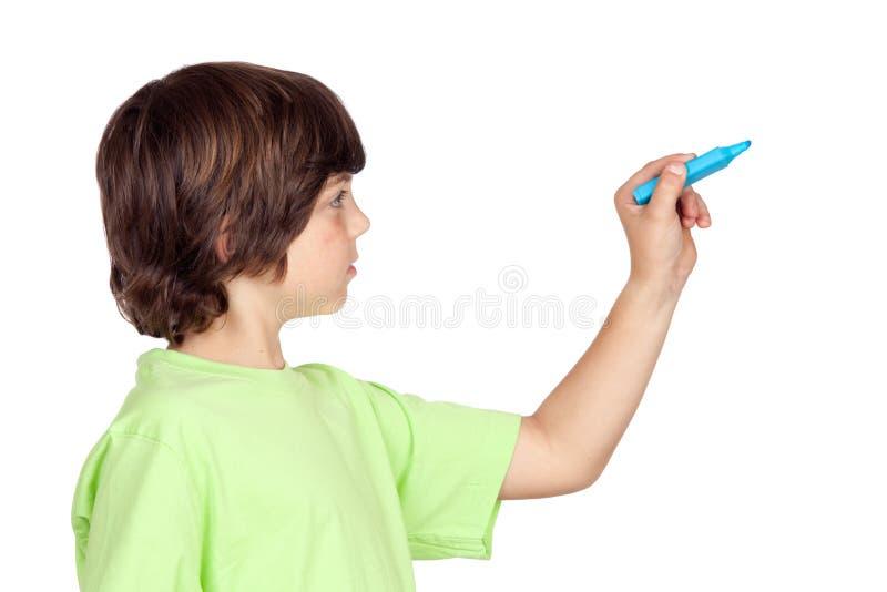 Niño con la escritura azul de la pluma foto de archivo libre de regalías
