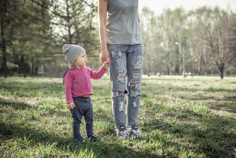 Niño con la madre que camina así como llevar a cabo las manos en parque del verano en hierba El tema principal es niño fotografía de archivo libre de regalías