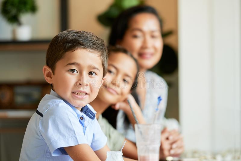 Niño con la madre y la hermana en café fotos de archivo libres de regalías