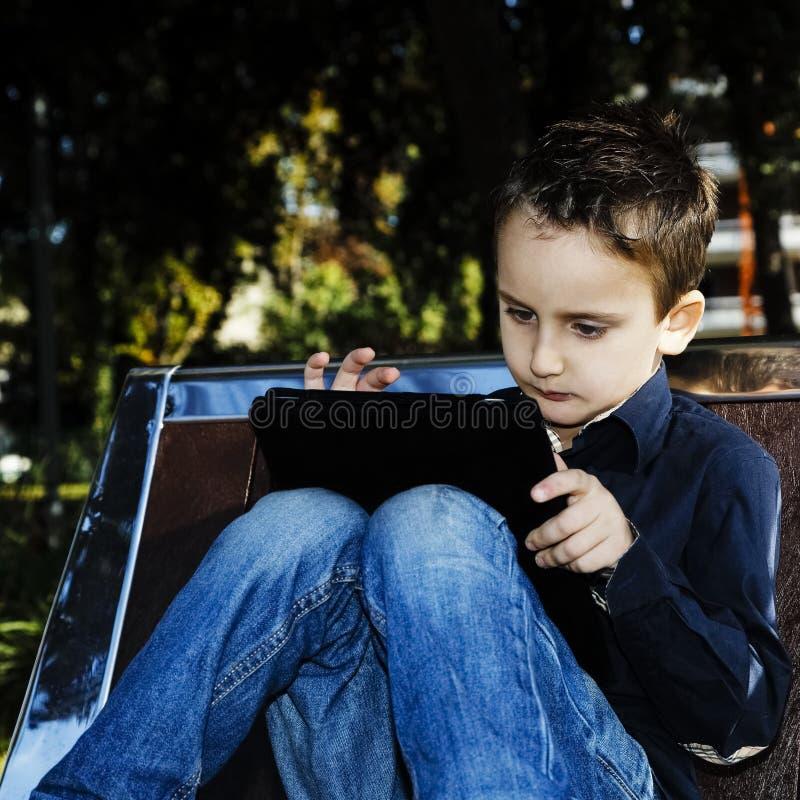 Niño con la tableta al aire libre en un parque fotografía de archivo