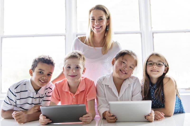 Niño con la tableta y el ordenador portátil de la tecnología en profesor de la sala de clase en el fondo foto de archivo