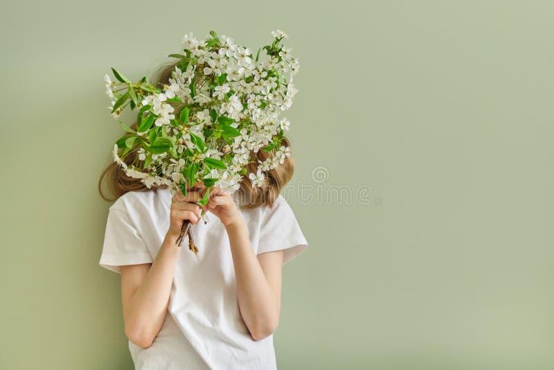 Niño con las ramas florecientes de la cereza de las flores blancas de la primavera, fondo verde de la pared, espacio de la muchac imágenes de archivo libres de regalías