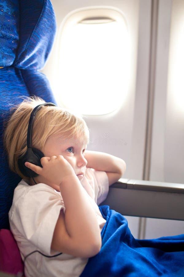 Niño con los auriculares en el avión imágenes de archivo libres de regalías