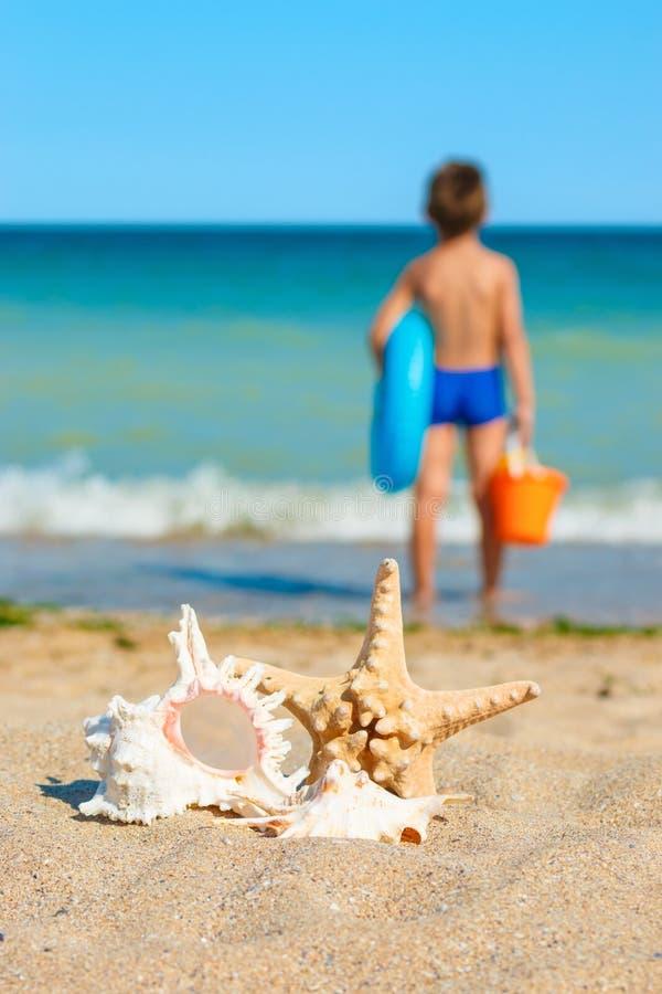 Niño con los juguetes, mirando el mar foto de archivo