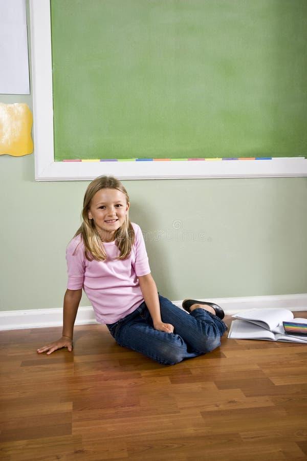 Niño con los libros que se sientan en suelo por la pizarra imagen de archivo
