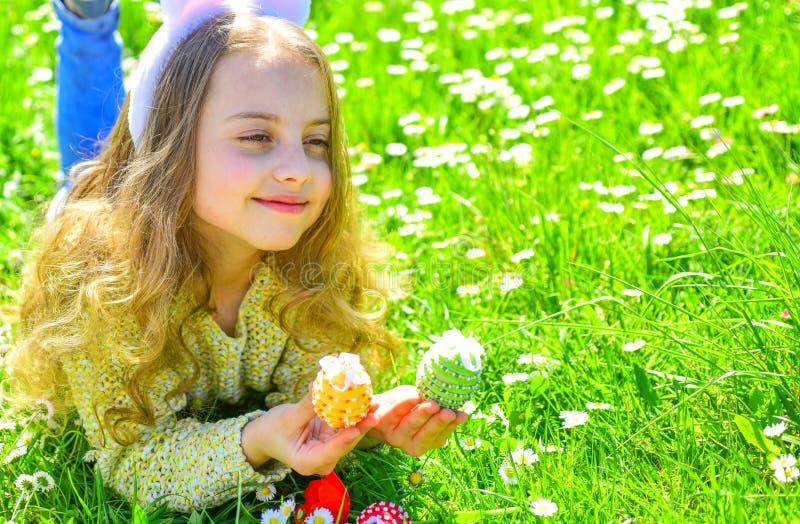 Niño con los oídos lindos del conejito que mienten en el prado El niño lindo pone en hierba con el huevo en manos Caza de la niña fotografía de archivo libre de regalías