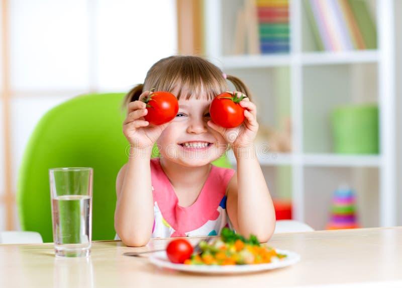 Niño con los tomates Muchacha feliz con las verduras en fotos de archivo