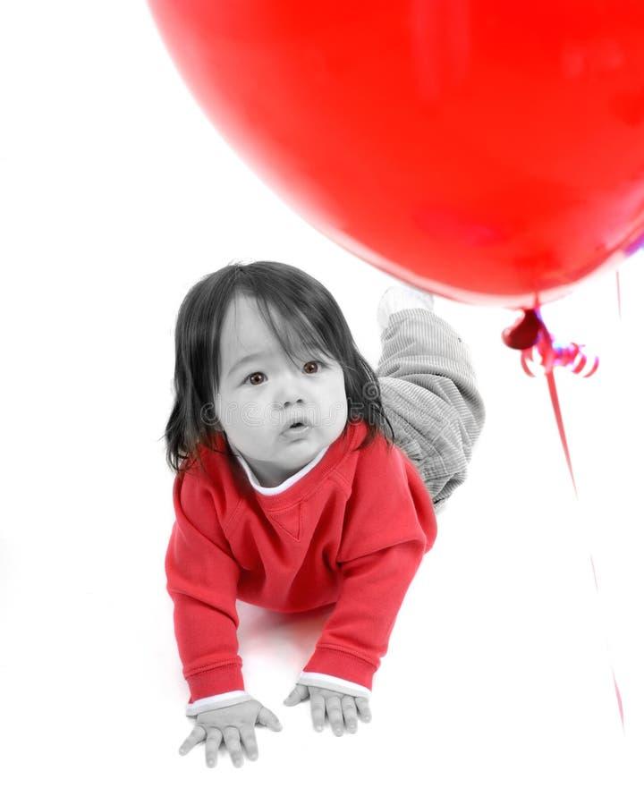 Niño con mirada roja de los globos fotografía de archivo