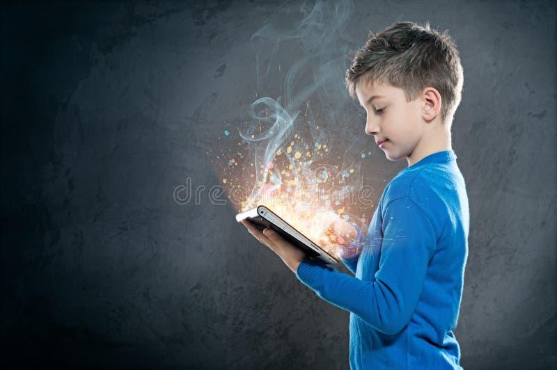 Niño con PC de la tableta imagen de archivo
