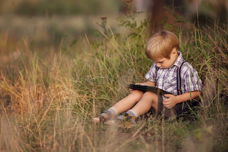 Niño con PC de la tableta al aire libre imagenes de archivo