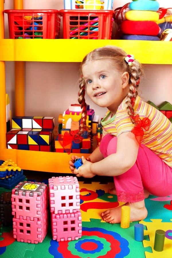 Niño con rompecabezas y bloque en sitio del juego. foto de archivo