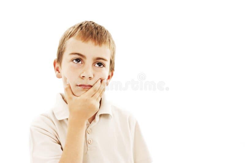 Niño con una expresión pensativa que mira para arriba imagenes de archivo