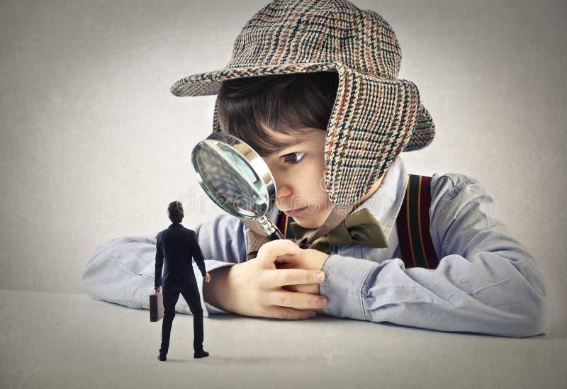 Niño con una lente de la mano que mira a un hombre de negocios imagenes de archivo