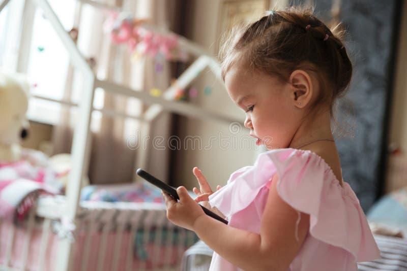 Niño concentrado de la niña dentro usando el teléfono móvil imágenes de archivo libres de regalías