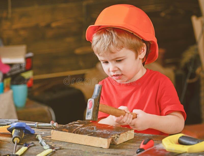 Niño concentrado que trabaja con el martillo Niño pequeño que gana nuevas habilidades Preescolar que aprende martillar el clavo fotografía de archivo