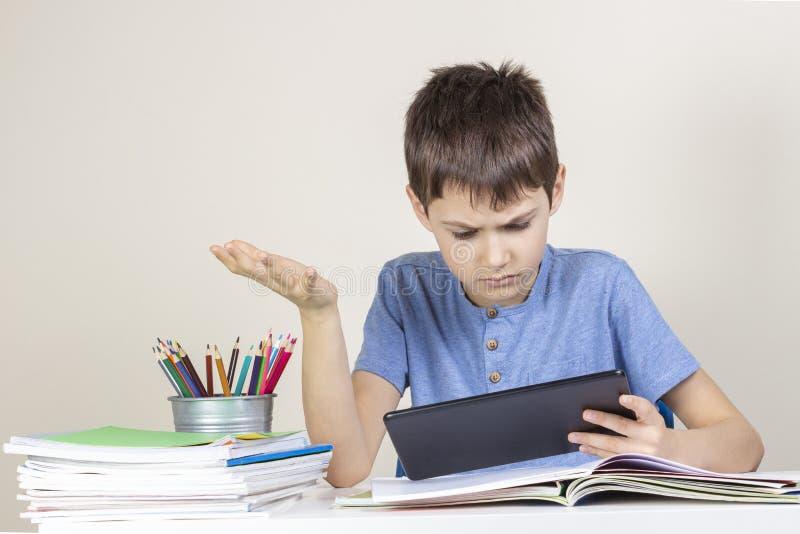Niño confundido, sorprendido con la tableta que se sienta en la tabla con los cuadernos de los libros fotografía de archivo libre de regalías