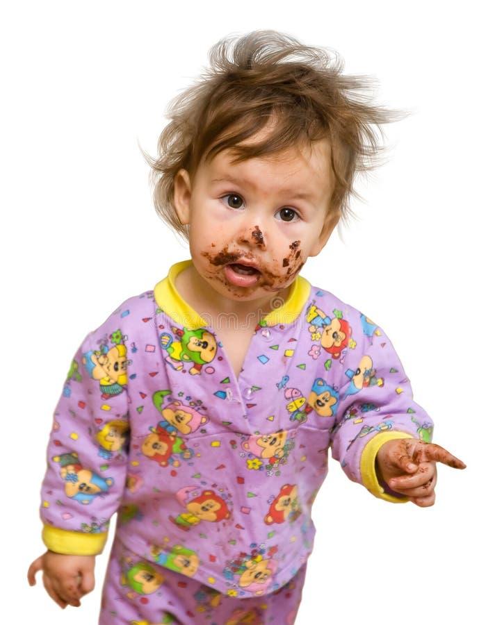 Niño curioso con la cara sucia del chocolate imagenes de archivo