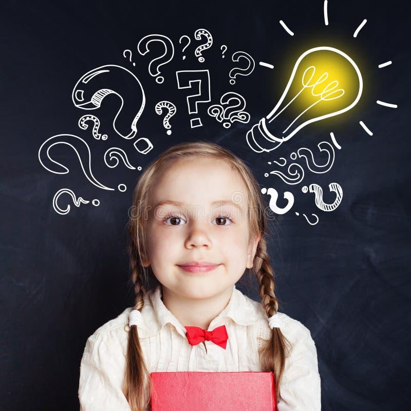 Niño curioso de la edad de escuela con el signo de interrogación de la bombilla y de la tiza imagen de archivo libre de regalías