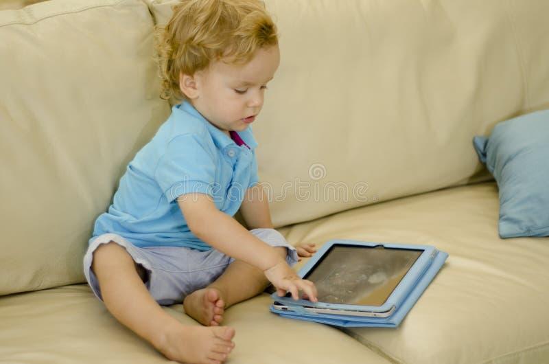 Niño curioso que juega con una tableta imágenes de archivo libres de regalías