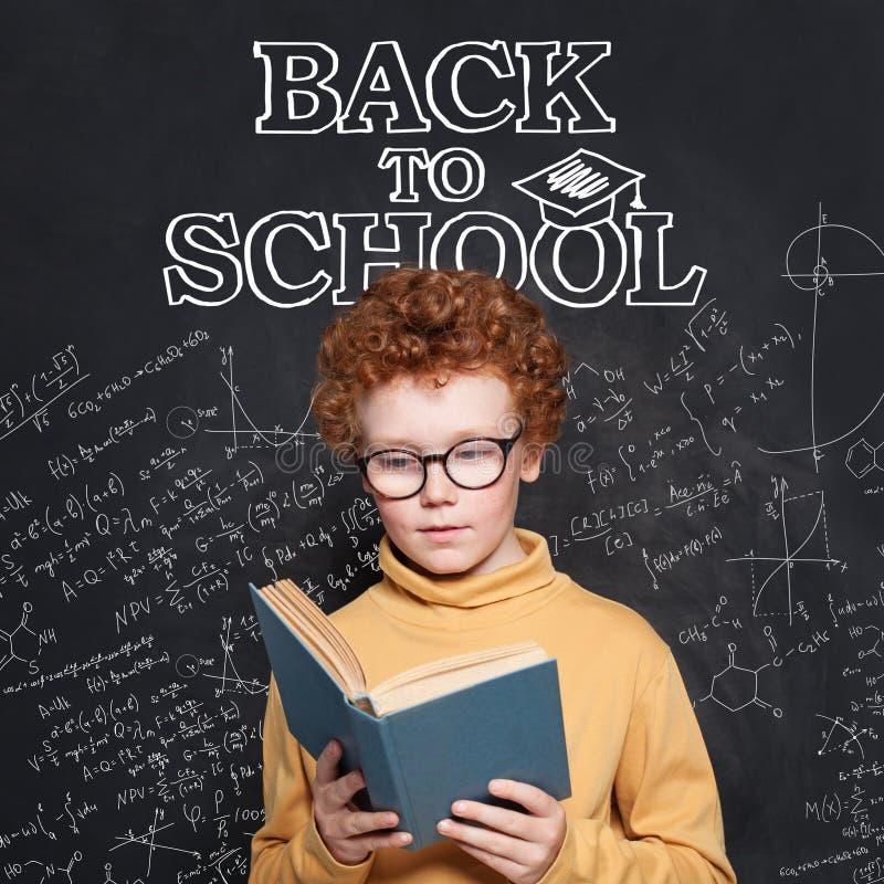 Niño curioso que lee un libro en fondo de la pizarra De nuevo a concepto de la escuela fotografía de archivo libre de regalías