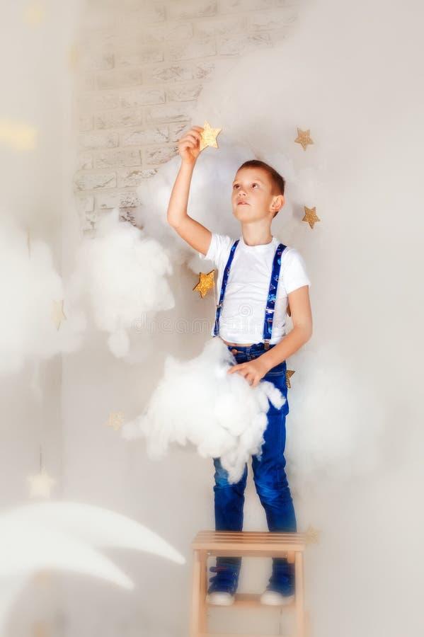 Nino De 6 Anos Con Pantalones Vaqueros Azules Y Tirante En La Escalera Con Nubes Y Estrella Tactil Los Suenos Se Hacen Realidad E Foto De Archivo Imagen De Estrella Azules 166865426