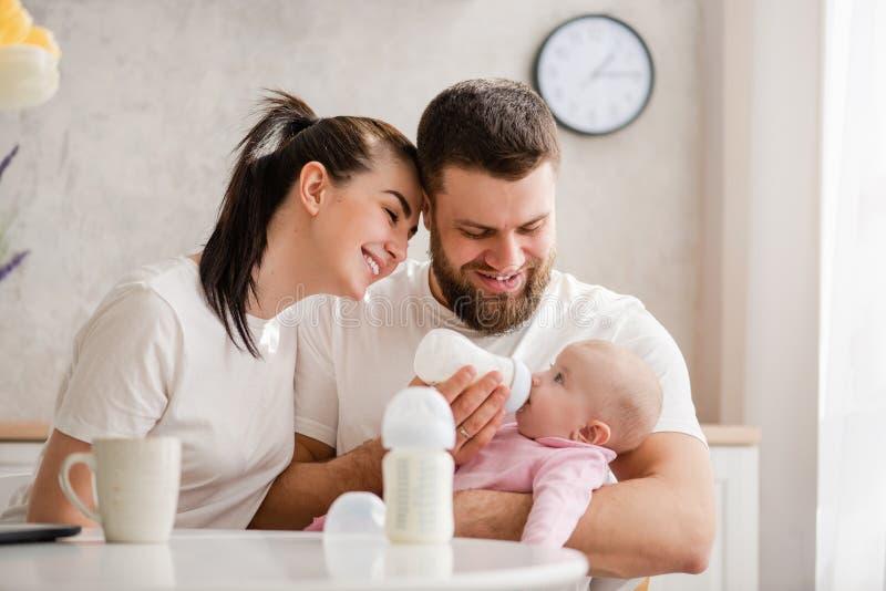 Niño de alimentación de los pares jovenes felices de la botella imagen de archivo libre de regalías